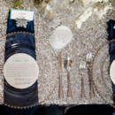 Glamorous silver sequin tablescape with dark blue napkins.