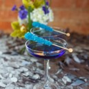 Dark blue wedding cocktail with aqua rock candy stirrers.