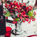 Centerpiece with red blooms and berries.