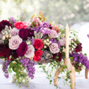 Lavish centerpiece with purple and ruby roses.