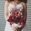 Bridal bouquet featuring red amaryllis, spray roses and berries.