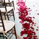 Red and pink ombre flower petals lining the aisle.