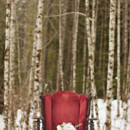 Ruby red velvet chair with bridal bouquet.