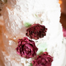 Tiered wedding cake with ruby red floral accents.