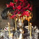 Tall, dramatic ruby red centerpiece with black feather.