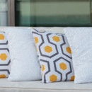 Decorative throw pillows in golden yellow and grey contemporary geometric pattern.