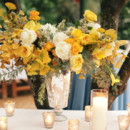 Centerpiece arrangement of golden yellow roses and leaves.