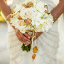 Stunning white bridal bouquet with golden yellow leaves.