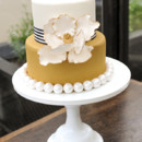 Golden yellow two-tone wedding cake with large floral embellishment.
