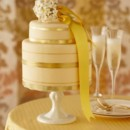 Elegant wedding cake with shiny gold bands and yellow satin ribbon.