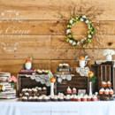 A rustic wedding cake and cupcake display