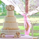 A lovely rustic buttercream wedding cake with raffia ribbon borders and burlap roses