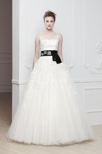 """Olga"" A-line tulle gown with illusion neckline. Lace applique adorning the bodice and trailing down to the skirt. Black belt with flower detail at natural waist."