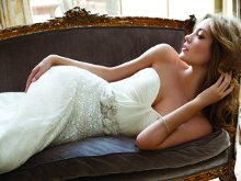 Tuula Ivory Strapless georgette dropped waist modified A-line bridal gown with draped sweetheart neckline, crystal encrusted skirt, and floral embellished satin sash at natural waist with chapel train. Available in Ivory only.
