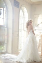 Kira, Style 6353  Ivory strapless A·line bridal gown with sweetheart lace bodice, silk georgette flounced skirt with chapel train. Offered with detachable lace cap sleeve bolero forming keyhole in front and back. (Shown with ivory over cashmere bodice)