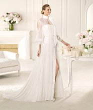 VALQUIRIA Valquiria from the Manuel Mota 2013 collection for Pronovias is made in soft chiffon. This light, blouson-style wedding dress has a shirt neckline that accentuates the bohemian style of its open sleeves and mother-of-pearl details around the neck and cuffs. The A-line skirt flares out below an embroidered sash that gathers the fabric of the bodice.