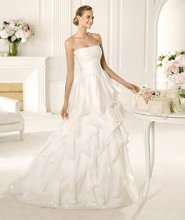 VINILO Vinilo from the Manuel Mota 2013 collection for Pronovias is made in delicate chiffon. This A-line wedding dress has an elegant skirt covered with frills that flow down to the hem. Bias cut organza skims the figure, while the off-the-shoulder neckline and soft draping accentuates its beauty.
