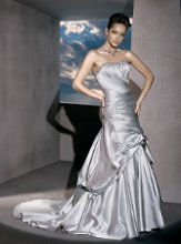 4289 Satin, Strapless with a beaded necklin, A-symmetrical pleating throughout gown and bustles on Fit'n'Flare Skirt and train. Gown also features a beaded motif on side skirt.