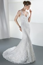 STYLE 1447 Lace, Sheath with a deep V-neckline, low. Sheer, beaded criss-cross back and attached train. Available in ivory and white