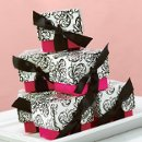 "Two-Piece Filigree Favor Boxes: These elegant two-piece favor boxes measure 2"" x 2"" x 2"" and feature black and white filigree patterned tops and brightly colored fuchsia bottoms. Pre-cut, ⅝"" black ribbons are included for easy customer assembly."