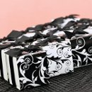 "Black and White Reversible Flourish Wrap Favor Boxes: These versatile white favor boxes measure 2"" x 2"" x 2"" and feature reversible wraps with black and white flourish designs. Pre-cut, ⅝"" black satin ribbons and double-sided tape for securing the wraps are included."