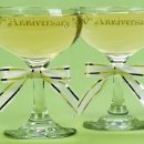 "50th Anniversary Champagne Toasting Glasses: These classic 50th anniversary champagne toasting glasses feature ""50th Anniversary"" in gold ink and are decorated with gold-edged white ribbon bows. Set of two glasses; each is 4½"" tall. Can be personalized with names and date."