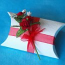 Red Rose Bouquet Pillow Box For a truly luxurious favour, why not try this embossed ivory pillow box. Hand-tied with a fabulous bouquet of red roses and finished with a glorious red ribbon, each box is filled with 5 red foiled chocolate hearts. Approximately 7cm long at the centre, 6.5 cm across, and 2.5cm deep, in packs of 10.