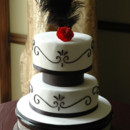 20's themed cake, in classic white and black, and adorned with a single red sugar rose for a pop of color, and an ostrich feather.