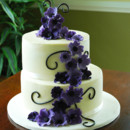 a buttercream wedding cake, in a left stacked configuration, with shades of purple flowers in a cascading pattern.