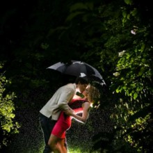 220x220 sq 1430936627378 engagement photo couple kissing under umbrella in