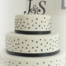 130x130 sq 1365609632318 fondant wedding cake with black ribbon dots and monogram
