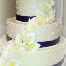 220x220 sq 1365609608725 buttercream wedding cake with purple fondant band dots and gumpaste calla lillies