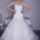 Heather  Tulle/Silk Organza. Dropped waist A-line gown. Strapless sweetheart neckline with ruched bodice which is accented with hand cut alencon lace. Skirt is accented with organza and layers of tulle and rows of lace.