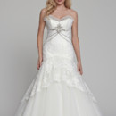 Dahlia Tulle/Hand Embroidered Chantilly lace. Fit to flair gown with high low lace skirt detail. Strapless sweetheart and tulle pleated neckline and low back. Crystal Swarovski beading, and covered buttons accent bodice. Cathedral train compliments the gown.