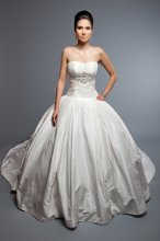 Daniela Silk Tissue Taffeta. Full Ball Gown. Strapless pleated dropped waist bodice, with box pleat skirt. Gown accented with hand beaded crystal applique at the empire line.