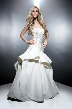 Liliana Heavy Silk Gazar. Dropped waist fit and flair gown with cascading peplum wave detail skirt. Strapless neckline bodice with ruching and accented with hand embroidery and crystals.