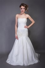 "Style ""Emma"" Silk Organza. Dropped waist slim strapless A-line gown with box pleats. Ruched neckline band detail at bust line and dropped waist line. Gown is accented with bias cut floral detail and crystals at drop waist and train."