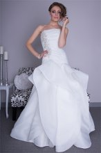 "Style ""LillianaB"" Satin Organza. Dropped waist fit and flair gown with cascading peplum wave detail skirt. Strapless neckline bodice with ruching and accented with crystals and hand embroidery."