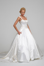 Amalia Silk Gardenia Satin. Ball gown with box pleated skirt and cathedral length train. Chandelier and floral beading adorn the drop waist bodice with curved neckline, beaded straps, and cathedral train.