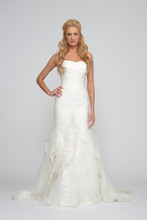 Brielle Organza. Trumpet gown with fluttered organza and lace skirt. Strapless sweetheart neckline with pleated bodice. Gown is accented with asymmetric re-embroidered hand appliqued lace