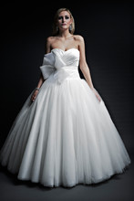 Eliana Silky Satin & Tulle. Full dropped waist gathered ball gown with poodle length train. Strapless slight deep neckline. Draped asymmetric bodice.
