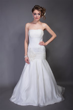 Emma Silk Organza. Dropped waist slim strapless A-line gown with box pleats. Ruched neckline band detail at bust line and dropped waist line. Gown is accented with bias cut floral detail and crystals at drop waist and train.