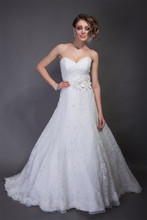 Eva Chantilly Lace. Modified A-line gown with cathedral train. Strapless sweetheart neckline with natural waist organza sash and flower detail. Hand rolled organza rossets accent the gown.