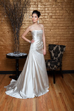 Nicole BMW Silk Satin. Draped column gown with fish tail. Strapless sweetheart neckline and sweep train. Hand embroidery beading, and ribbon detail accenting the side of the gown.