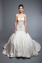 Saundra Duchess Silk Satin. Fit and flair ball gown. Strapless sweetheart neckline with beaded illusion. Draped bust and dropped waist. Fully beaded and embroidered bodice and skirt.