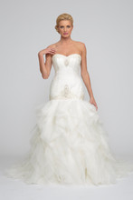 Anastasia Organza. Fit to flair gown with layers of frothy organza raw edge ruffle detail. Strapless sweetheart neckline. Asymmetric crisscross pleated bodice accented with delicate beading at neckline and drop waist. Cathedral length train.
