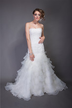 Bernice  Organza.  Dropped waist A-line gown with tiered asymmetric tiered organza ruffled skirt and chapel train.  Strapless slight dip neckline with lace and beaded bodice.
