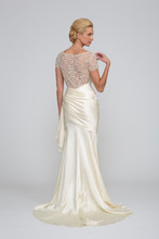 Candace  Silk Charmeuse. Sheath gown with draped asymmetric waist line. Sweetheart neckline and draped bodice. Bodice accented with beaded illusion sleeves and back. Chapel length train.