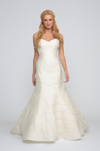 Kate Silk Organza. Trumpet gown with organza asymmetric layers and chapel length train. Tulip pleated sweetheart neckline accented with double spaghetti straps which crisscross over the back.