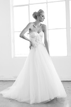 Orchid Silk Tulle. Curved drop waist gown with full A-line skirt and chapel length train. Strapless sweetheart neckline bodice with asymmetric floral beading accent the bodice.